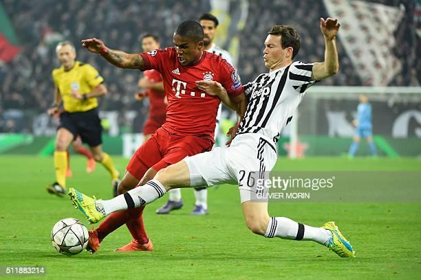 Juventus' Swiss defender Stephan Lichtsteiner challenges Bayern Munich's Brazilian midfielder Douglas Costa during the UEFA Champions League round of...