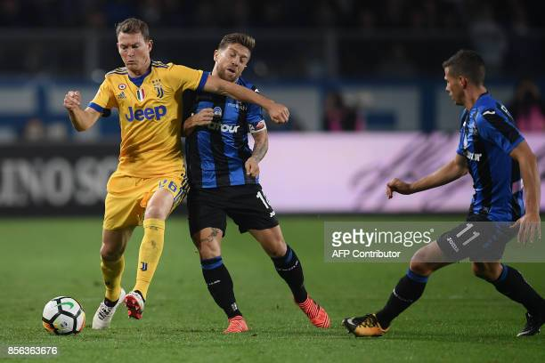 Juventus' Swiss Stephan Lichtsteiner fights for the ball with Atalanta's Argentinian forward Papu Gomez during the Italian Serie A football match...
