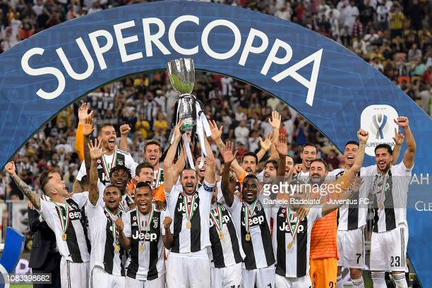 Juventus team celebrate with the trophy after winning the Italian Supercup match between Juventus and AC Milan at King Abdullah Sports City on...