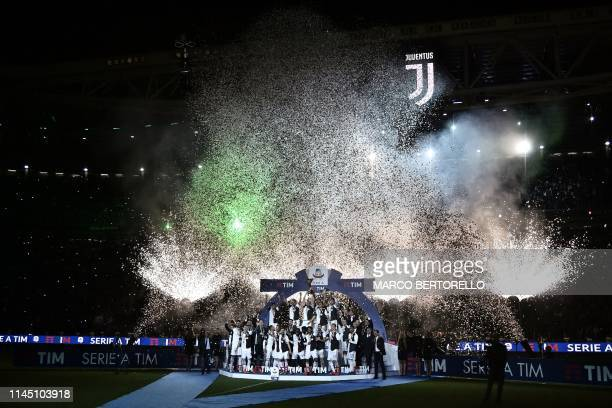 TOPSHOT Juventus team players celebrate with the Italian Champion's trophy at the end of the Italian Serie A football match Juventus vs Atalanta on...
