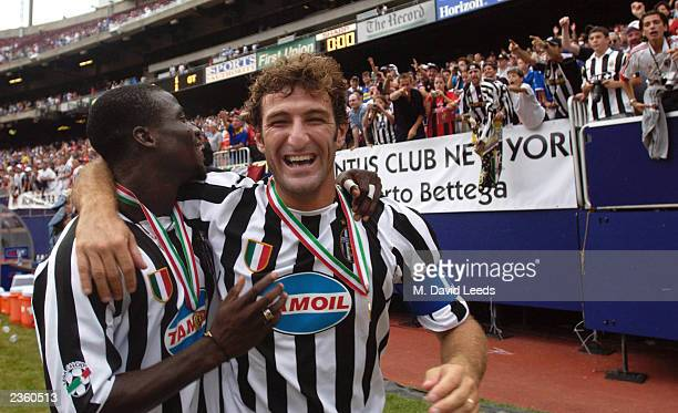 Juventus teammates Stephen Appiah and Ciro Ferrara take a victory lap around the field following their team's victory over AC Milan in the Supercoppa...