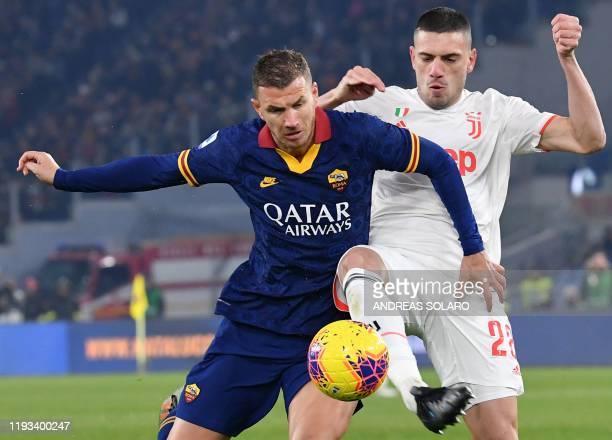 Juventus' Turkish defender Merih Demiral tackles AS Roma's Bosnian forward Edin Dzeko during the Italian Serie A football match AS Roma vs Juventus...