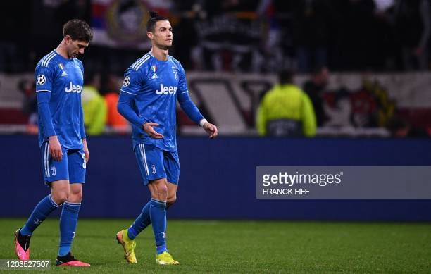 Juventus' Uruguayan midfielder Rodrigo Bentancur and Juventus' Portuguese forward Cristiano Ronaldo react after the UEFA Champions League round of 16...