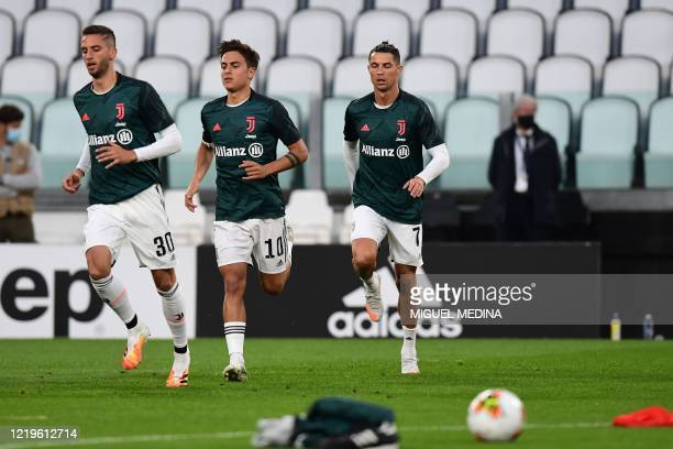 Juventus' Uruguayan midfielder Rodrigo Bentancur, Juventus' Argentine forward Paulo Dybala and Juventus' Portuguese forward Cristiano Ronaldo warm up...