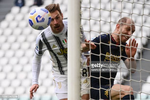 Juventus' Welsh midfielder Aaron Ramsey attempts to score a header despite the defence of Genoa's Italian defender Andrea Masiello during the Italian...