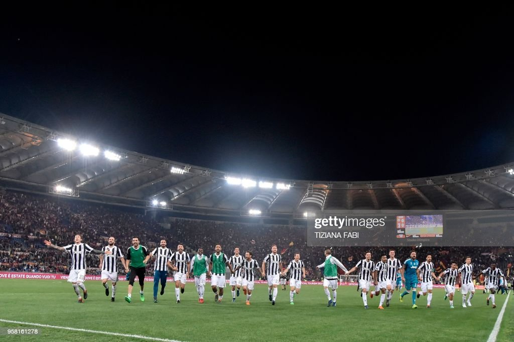 Juventus'players celebrate at the end of the Italian Serie A football match AS Roma vs Juventus at the Olympic stadium on May 13, 2018 in Rome. Juventus won a seventh straight Serie A title on Sunday after a goalless draw against ten-man Roma at the Stadio Olimpico. - The Turin giants become the first team to complete the league and Cup double for four consecutive seasons. It is the 34th Scudetto in Juventus's history.