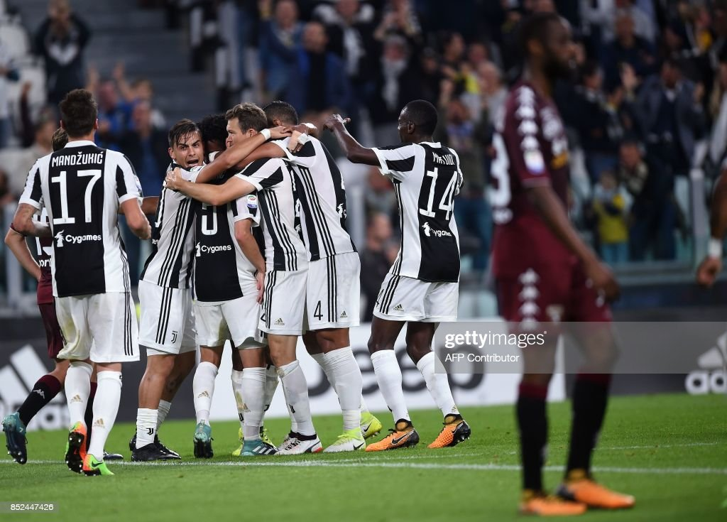 Juventus's midfielder from Bosnia-Herzegovina Miralem Pjanic (not pictured) is celebrated by teammates after scoring during the italian Serie A football match Juventus vs Torino at the Allianz Stadium in Turin on September 23, 2017. /