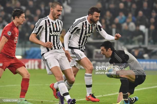 Juve's goalkeeper Gianluigi Buffon makes a save in front of teammates Andrea Barzagli and Leonardo Bonucci and Munich's Robert Lewandowski during the...