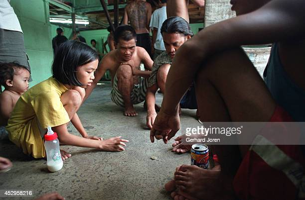 Juvilyn gambles with inmates, while her younger sister Jasmine watches the game, in a cell barrack at Manila City Jail. Their father Jaime is a...