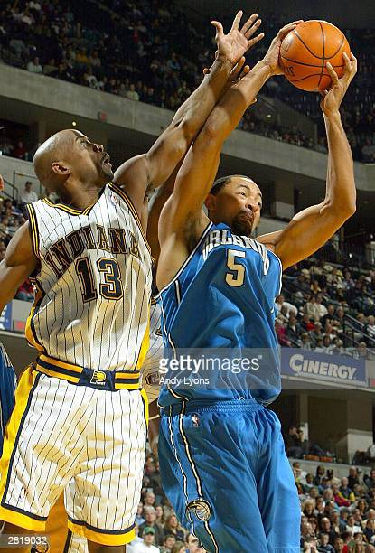 Juwan Howard of the Orlando Magic and Kenny Anderson#13 of the Indiana Pacers go for a rebound on December17 2003 at Conseco Fieldhouse in...