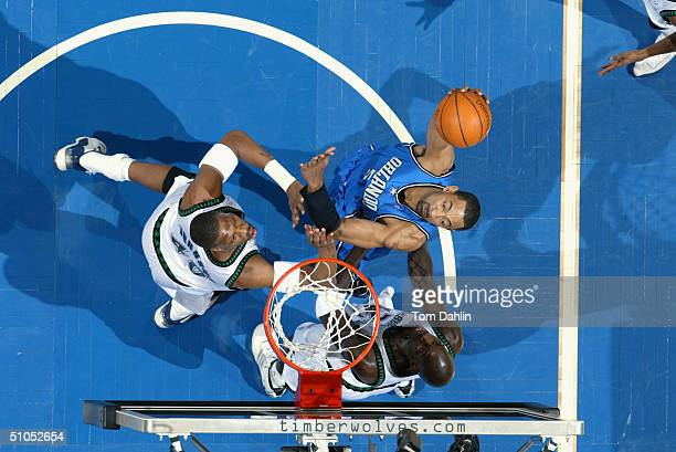 Juwan Howard of the Orlando Magic goes up for a shot against Ervin Johnson and Kevin Garnett of the Minnesota Timberwolves during the game at Target...