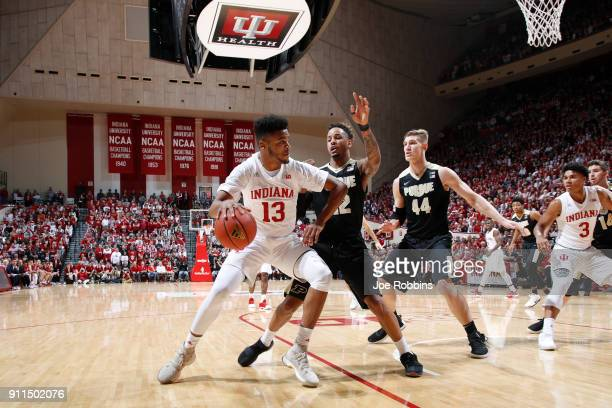 Juwan Morgan of the Indiana Hoosiers looks to the basket while defended by Vincent Edwards and Isaac Haas of the Purdue Boilermakers in the first...