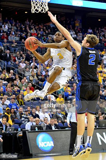 Juwan Staten of the West Virginia Mountaineers drives to the basket against Jevon Carter of the West Virginia Mountaineers in the first half during...