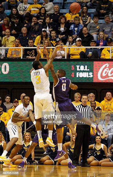 Juwan Staten of the West Virginia Mountaineers pulls up for a three against Charles Hill Jr #0 of the TCU Horned Frogs during the game at the WVU...