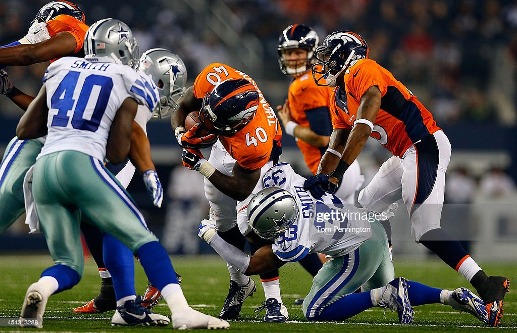Juwan Thompson #40 of the Denver Broncos is tackled by Ryan Smith #33 of the Dallas Cowboys in the second half of their preseason game at AT&T Stadium on August 28, 2014 in Arlington, Texas.