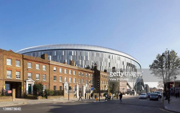 Juxtaposition of stadium facade to terraced housing. The New Tottenham Hotspur Stadium, London, United Kingdom. Architect: Populous, 2019.