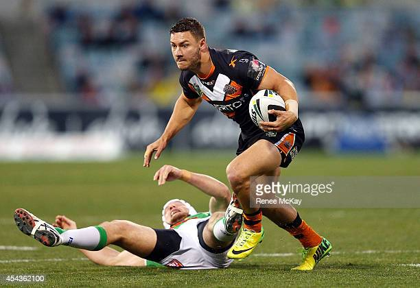 Jy Hitchcox of the Tigers gets away from Jarrod Croker of the Raiders during the round 25 NRL match between the Canberra Raiders and the Wests Tigers...
