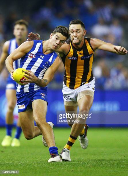 Jy Simkin of the Kangaroos runs with the ball from Jack Gunston of the Hawks during the round five AFL match between the North Melbourne Kangaroos...