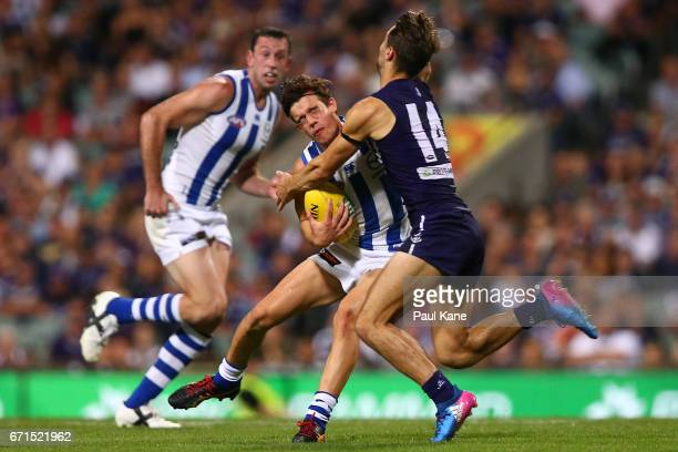 Jy Simpkin of the Kangaroos gets tackled by Lachie Weller of the Dockers during the round five AFL match between the Fremantle Dockers and the North...