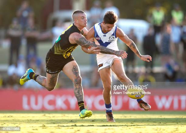 Jy Simpkin of the Kangaroos is tackled by Dustin Martin of the Tigers during the AFL 2018 JLT Community Series match between the Richmond Tigers and...