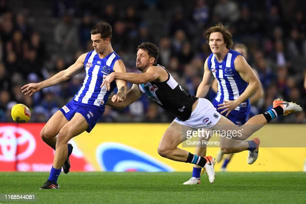 Jy Simpkin of the Kangaroos kicks whilst being tackled by Travis Boak of the Power during the round 22 AFL match between the North Melbourne...