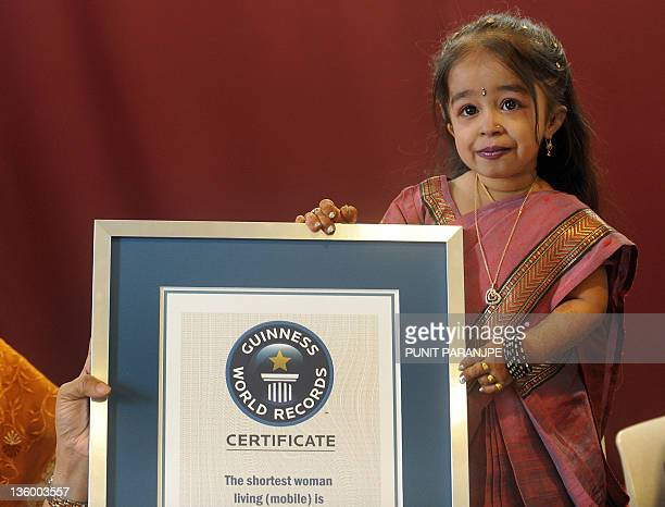 Jyoti Amge poses with an official certificate from Guinness World Records in Nagpur on December 16 2011 Amge was officially announced by the Guinness...