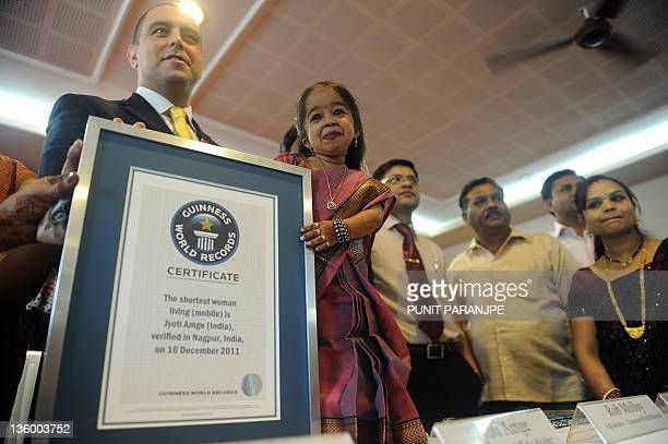 Jyoti Amge poses with Guinness World Records Adjudicator Rob Molloy during a news conference in Nagpur on December 16 2011 Amge was officially...
