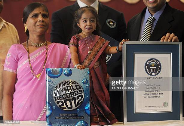 Jyoti Amge poses with her mother Ranjana and an official certificate from Guinness World Records in Nagpur on December 16 2011 Amge was officially...