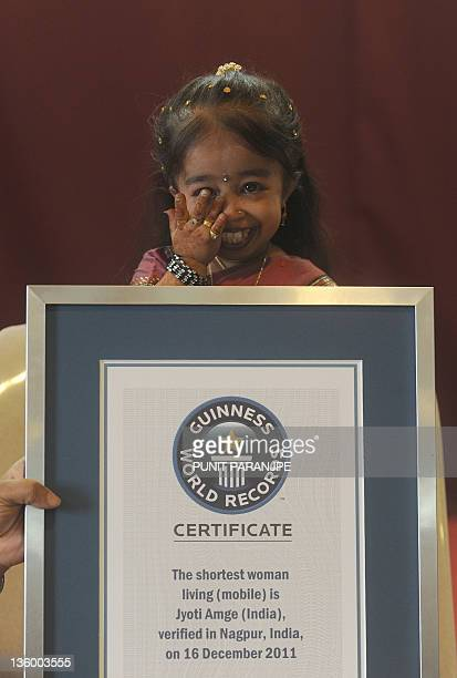 Jyoti Amge wipes a tear after receiving an official certificate from Guinness World Records in Nagpur on December 16 2011 Amge was officially...