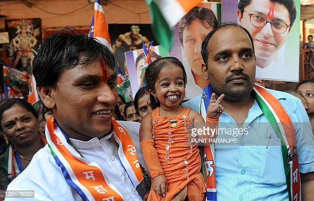 Jyoti Amge world's shortest woman living flashes a victory sign as she poses while campaigning for a local political party in Mumbai on February 7...
