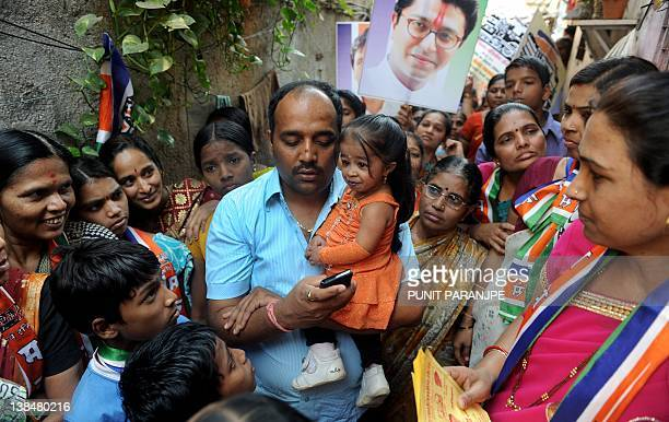 Jyoti Amge world's shortest woman living is carried by a party suppoter as others watch while campaigning for a local political party in Mumbai on...