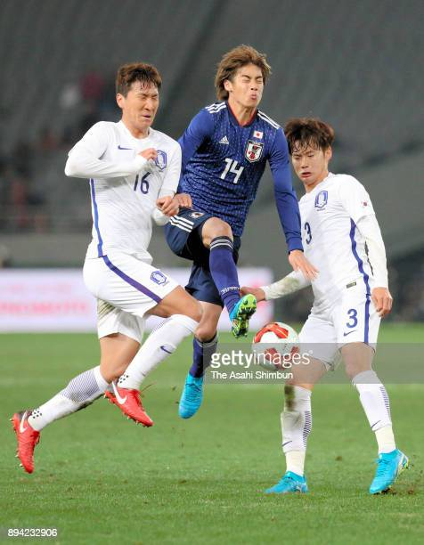 Jyunya Ito of Japan competes for the ball against Jung Wooyoung and Kim Jinsu of South Korea during the EAFF E1 Men's Football Championship between...