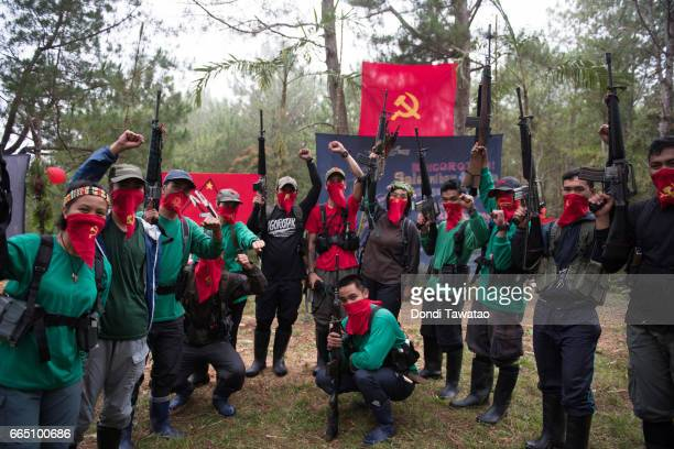 Ka Guillen and Ka Nancy raise their firearms in salute with guerillas of the New People's Army after the conclusion of their wedding on April 2 2017...