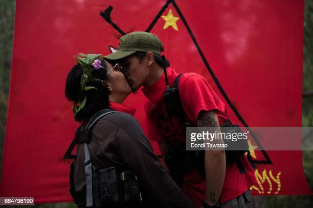 Ka Nancy and Ka Guillen kiss before the red flag of the New People's Army during their simple wedding rites on April 2 2017 in the remote hinterlands...