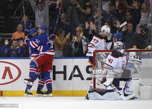 Kaapo Kakko of the New York Rangers celebrates his first NHL goal at 1828 of the first period against the Edmonton Oilers as he is embraced by Ryan...