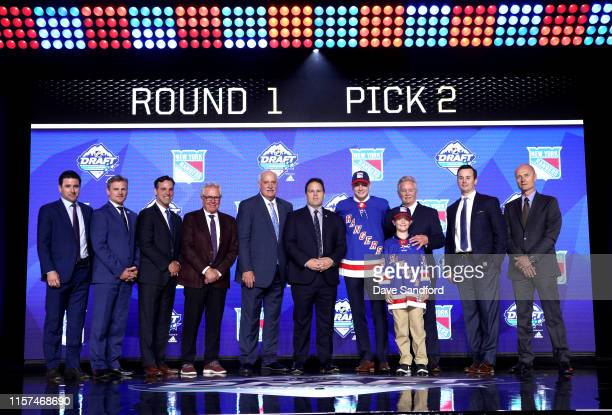 Kaapo Kakko second overall pick by the New York Rangers poses for a photo with team personnel onstage during the first round of the 2019 NHL Draft at...