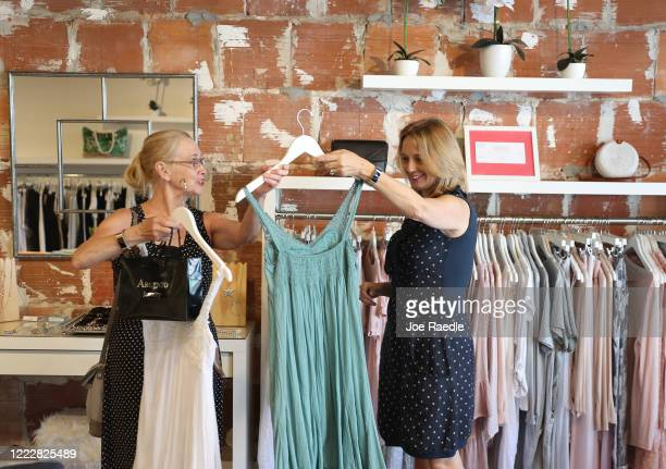 Kaarina Wardell helps Barbara White look at dresses as she shops at the MUST boutique store, as the state of Florida enters phase one of the plan to...
