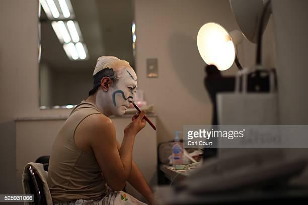 Kabuki actor Shido Nakamura applies his makeup as he prepares to perform in a final dress rehearsal for the kabuki theatre show 'Hanakurabe...