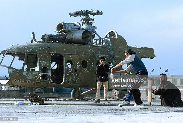 Afghan cricketers take part in a match on a patch of ground in front of a destroyed helicopter in Kabul17 March 2006 Cricket is popular among Afghans...