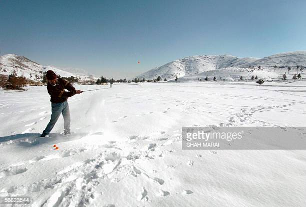 Afghan golfer Mohammed Afzal plays a shot during a practice session at the snow covered Kabul Golf Club 19 January 2006 After decades of neglect and...