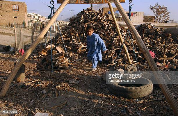 An Afghan boy caries wood to weigh on a scale in Kabul 12 December 2005 Despite the flood of billions of dollars of aid by the international...