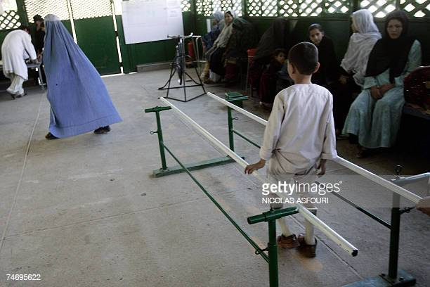 An Afghan boy who has polio tries his new pair of calipers in the exercise room at the International Committee of the Red Cross Orthopaedic centre in...