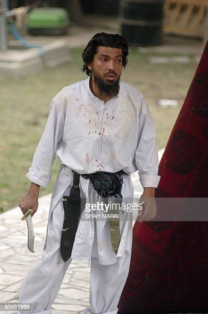 An Afghan man wielding a bowie knife stands after he wounded two colleagues in Kabul 29 April 2006 After two hours of confrontation the man was...