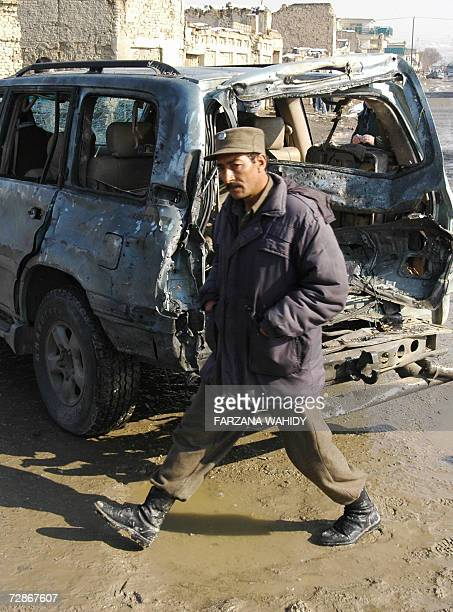 An Afghan policeman walks past the damaged car of member of parliament Padshah Khan Zadran after a suicide attack in Kabul 22 December 2006 The...