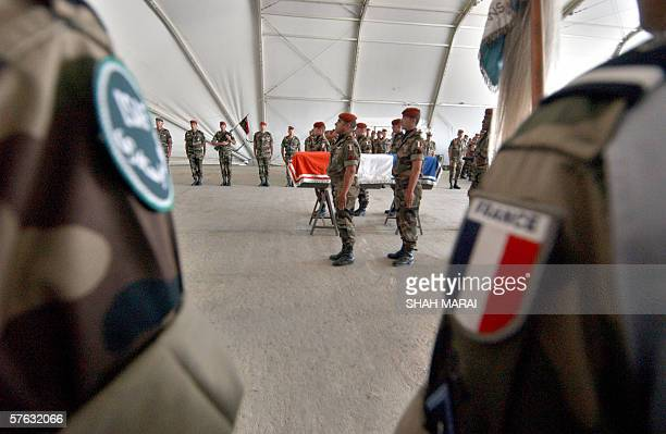 French soldiers from the International Security Assistance Force stand to attention near the coffin of a French soldier during a ceremony at Kabul...