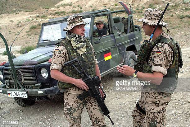 German troops from the International Security Assistance Force patrol the Butkhak district of southern Kabul where one of their comrades was killed...
