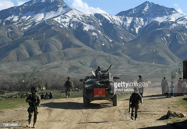 Italian soldiers of the NATO-led International Security Assistance Force walk besides an armoured car during a patrol on the outskirts of Kabul, 05...