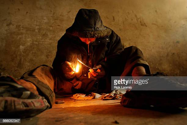Kabul, Afghanistan –– Mohammed Jawad Rezaie smokes heroin inside the abandoned Russian Cultural Center where he spends the majority of his time doing...