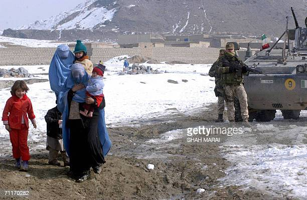 Picture taken 22 January 2006 of Italian soldiers of the International Security Assistance Force standing guard while Afghan women and children walk...