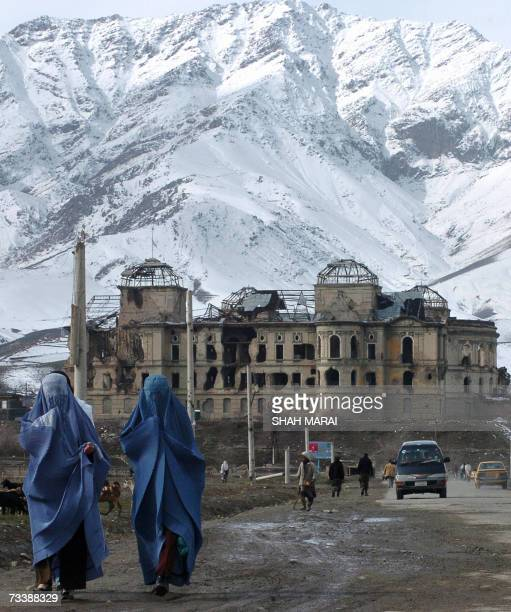 Two burqaclad Afghan women walk past the war damaged Darlaman Palace in the west of Kabul 22 February 2007 West Kabul was the scene of some of...